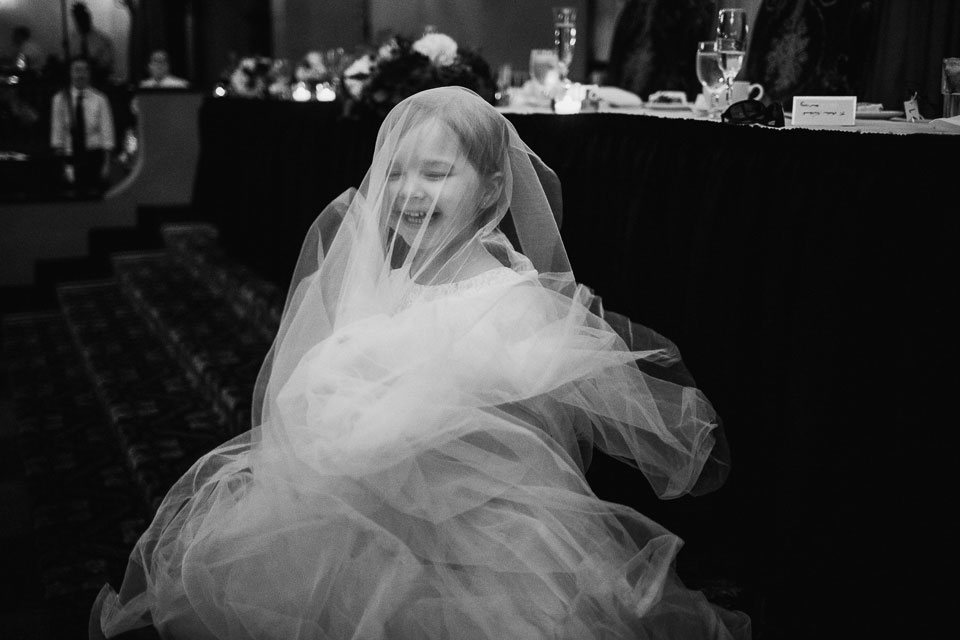 photo of cute flower girl at the wedding playing with her dress | statler city | buffalo ny