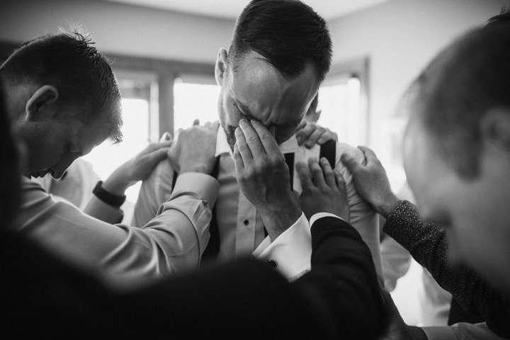 Groom and his groomsmen praying before wedding