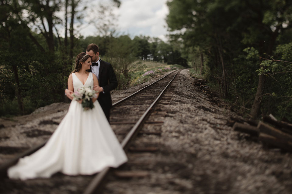 Portrait of the bride and groom on train tracks