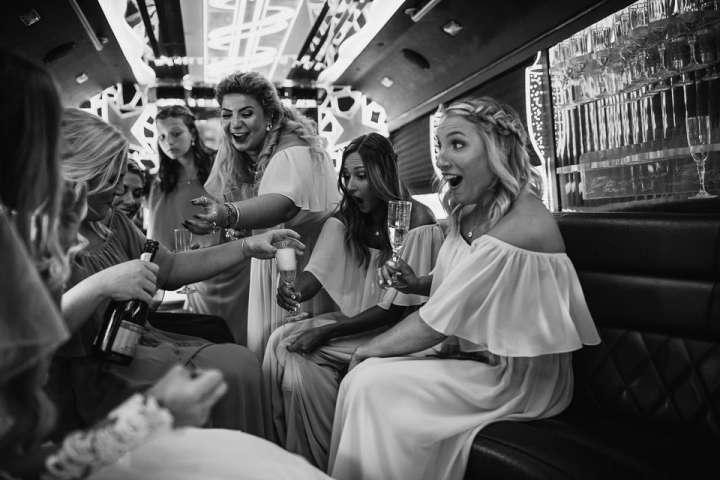 Bride with Bridesmaids in limo having fun